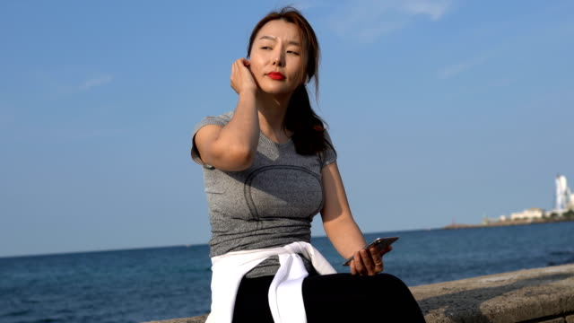 vidéos et rushes de a woman sitting and using a smart phone at the seaside - communication sans fil
