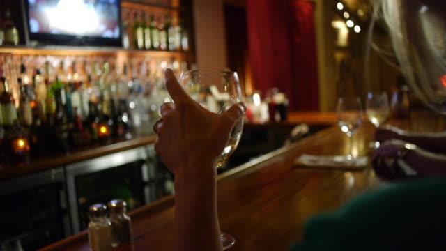 a woman sitting at a bar picks up a wine glass. - bar点の映像素材/bロール