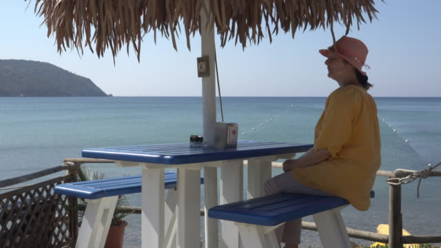 A woman sitting at a beach bar and looks out to the sea