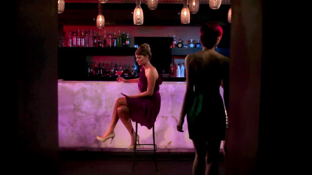 woman sitting at cocktail bar - bar点の映像素材/bロール