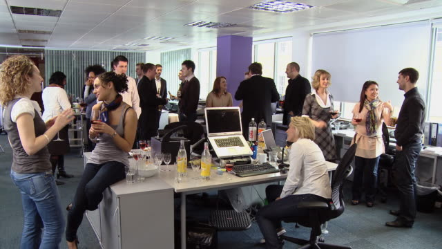 ws woman sitting at desk during office party as coworkers stand around talking and drinking/ london, england - after work stock videos & royalty-free footage
