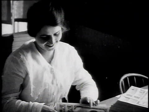 stockvideo's en b-roll-footage met woman sitting at desk flipping through liberty bonds / united states - 1917