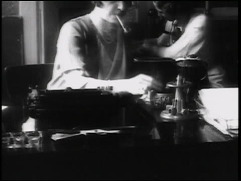 B/W 1938 woman sitting at desk in front of typewriter lighting pipe / newsreel