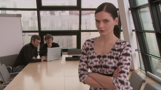 ms zi woman sitting at edge of conference table while two businessmen use laptop behind her / berlin, germany - female with group of males stock videos & royalty-free footage