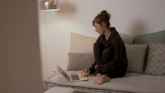 woman sitting at home on sofa looking at laptop - illness stock videos & royalty-free footage