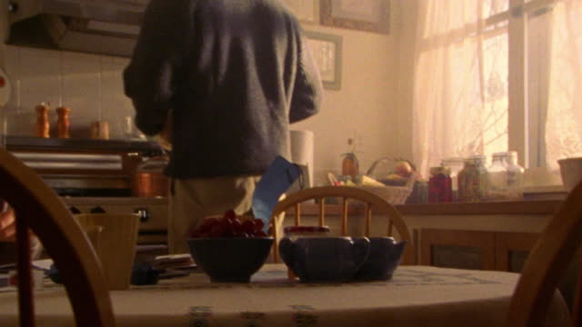 vídeos y material grabado en eventos de stock de canted pan woman sitting at kitchen table licking envelopes with man standing + answering phone - teléfono sin cable