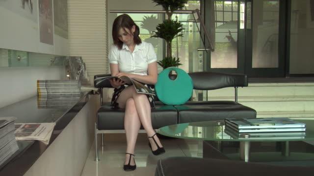 WS TU PAN Woman sitting at office reception being met by man / London, UK
