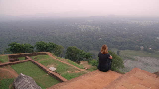ws woman sitting at ruins on hilltop looking at scenic landscape view,sri lanka - sri lanka stock videos & royalty-free footage