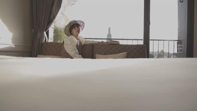frau sitzt auf sofa mit ikonischen tempel in bangkok hintergrund verschwimmen - serene people stock-videos und b-roll-filmmaterial