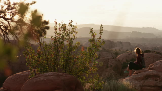 woman sitting at sunset near canyonlands, moab - remote location phone stock videos & royalty-free footage