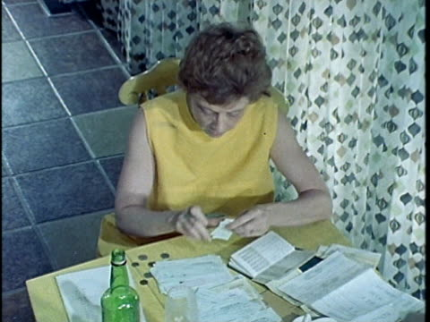 1971 ms ha woman sitting at table and paying bills, looking at empty bottle, los angeles, california, usa, audio   - financial bill stock videos & royalty-free footage