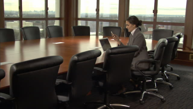 MS Woman sitting at table in conference room, text messaging on mobile phone/ Woman turning to smile at camera/ Montclair, New Jersey