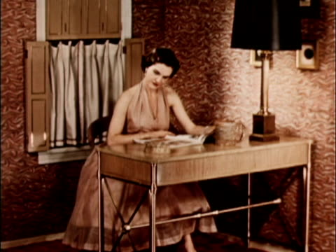 1956 montage woman sitting at table leafing through magazine in room / usa - magazine stock videos & royalty-free footage