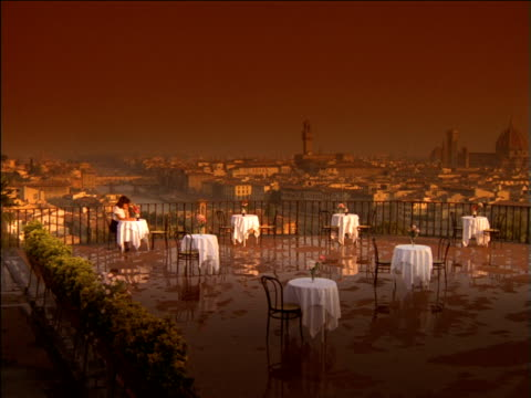 woman sitting at table of roof terrace restaurant at sunset with ponte vecchio bridge in distance, florence - postura video stock e b–roll