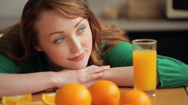 MH DS Woman Sitting at Table with Oranges and Orange Juice