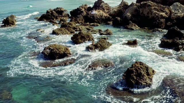 Frau sitzt auf den Felsen fallen das Meer