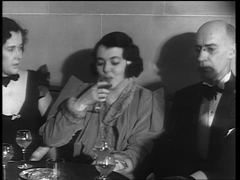 b/w 1933 woman sitting between woman man drinking from glass / end of prohibition - anno 1933 video stock e b–roll