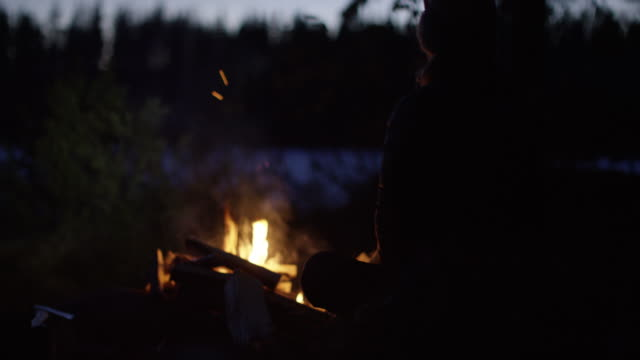 woman sitting by a campfire at night - campfire stock videos & royalty-free footage