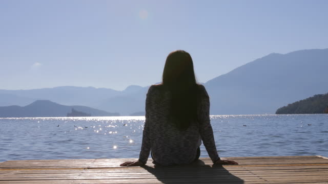 woman sitting by lake - yunnan province stock videos and b-roll footage