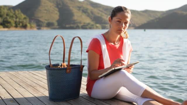 stockvideo's en b-roll-footage met woman sitting by lake writing diary - steiger pier