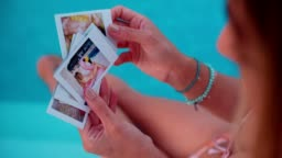 Woman sitting by pool looking at summer holidays polaroids