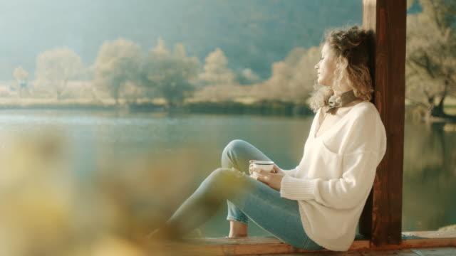 vídeos y material grabado en eventos de stock de mujer sentada en el lago y tomar café - escena de tranquilidad