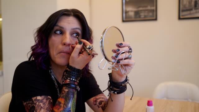 vidéos et rushes de femme s'asseyant par le miroir et appliquant le maquillage - piercing