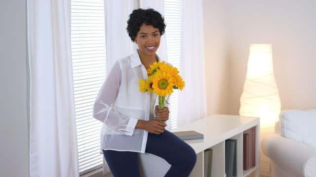 vídeos de stock e filmes b-roll de woman sitting by window holding sunflowers - fotografia de três quartos