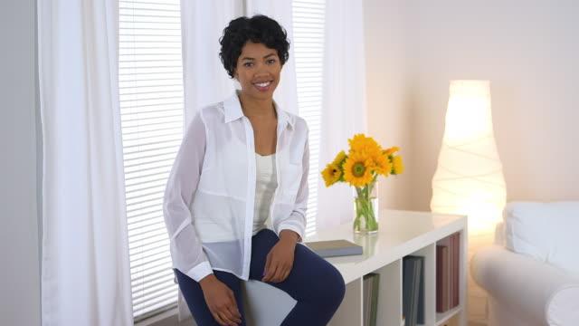 vidéos et rushes de woman sitting by window holding sunflowers - cadrage aux genoux