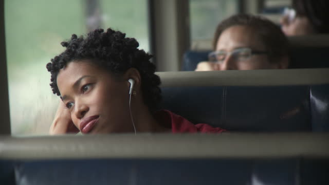 vidéos et rushes de cu woman sitting by window in moving train, listening to music on portable media player and talking on mobile phone / new york city, new york, usa - train de banlieue