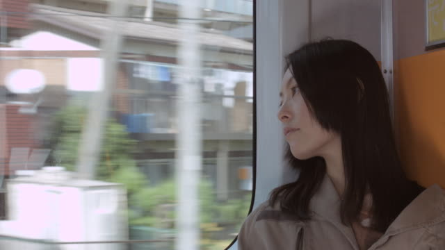 ms woman sitting by window on train / nerima, tokyo, japan - 瞑想する点の映像素材/bロール