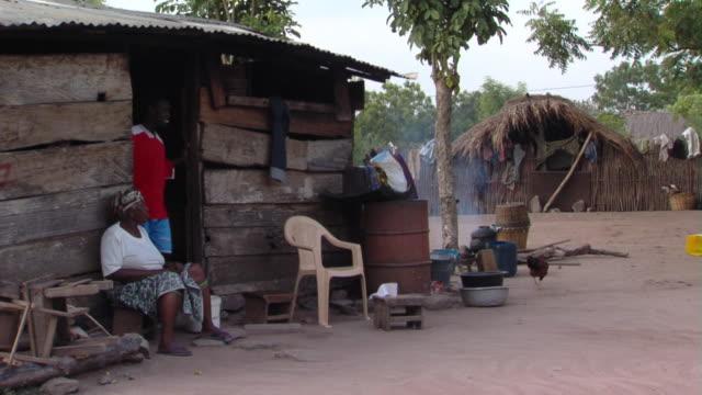 ms woman sitting by wooden shack, teenage boy walking outside, tamale, ghana - 草葺小屋点の映像素材/bロール