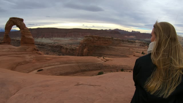 woman sitting close to delicate arch, arches national park - langes haar stock-videos und b-roll-filmmaterial