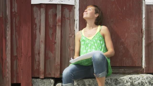 vídeos de stock e filmes b-roll de a woman sitting close to the wall huvudskar stockholm archipelago sweden. - apanhar sol