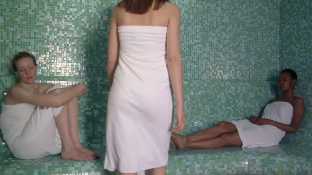 stockvideo's en b-roll-footage met ws zi cu woman sitting down next to two other women relaxing in sauna / norcia, italy  - sauna