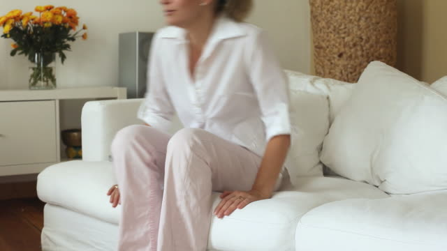 ms ds woman sitting down on couch and using remote control / potsdam, brandenburg, germany - cross legged stock videos & royalty-free footage