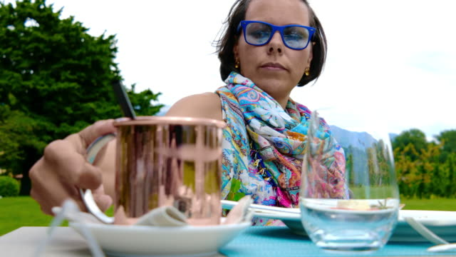 woman sitting in a outdoors restaurant and mixing her cocktail - mug stock videos and b-roll footage