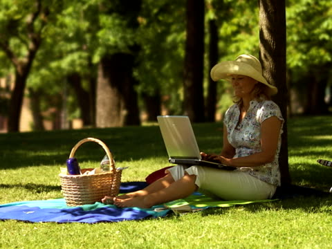 woman sitting in a park using her laptop after a while she shuts it off and takes a break sweden. - hot desking stock videos & royalty-free footage