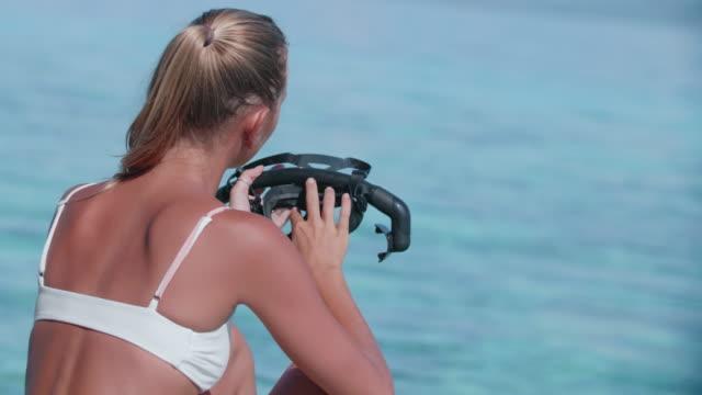 vídeos y material grabado en eventos de stock de a woman sitting in a white bikini with a snorkel mask, swimwear swimsuit on vacation at a tropical island hotel resort. - equipo de buceo