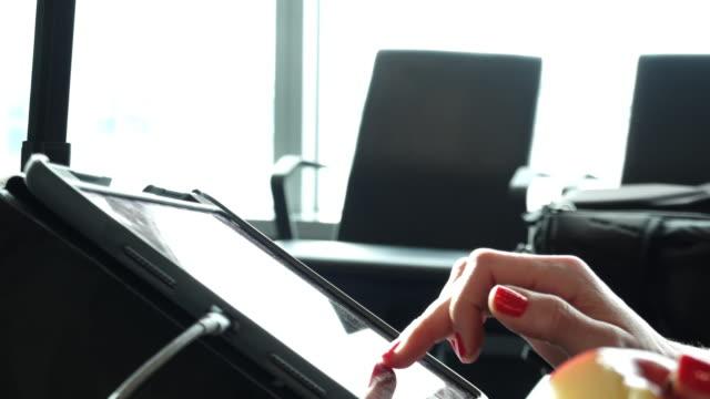 vídeos y material grabado en eventos de stock de mujer sentada en el salón del aeropuerto usando tableta, ventana con aviones detrás - esmalte de uñas rojo