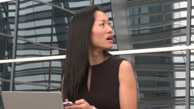 ms woman sitting in airport with laptop on lap and appearing frustrated as she uses pda/ virginia beach, virginia - chinese ethnicity stock videos & royalty-free footage