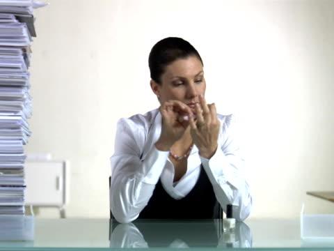 vídeos y material grabado en eventos de stock de a woman sitting in an office polishing her nails when a pile of paper next to her grows higher, sweden. - secretaria