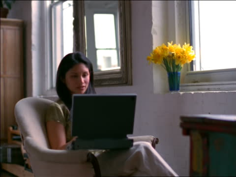woman sitting in armchair by window working on laptop computer - 1998 stock videos and b-roll footage