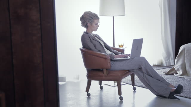 MS Woman sitting in armchair in old fashioned hotel room while working on laptop / Palmdale, CA, United States
