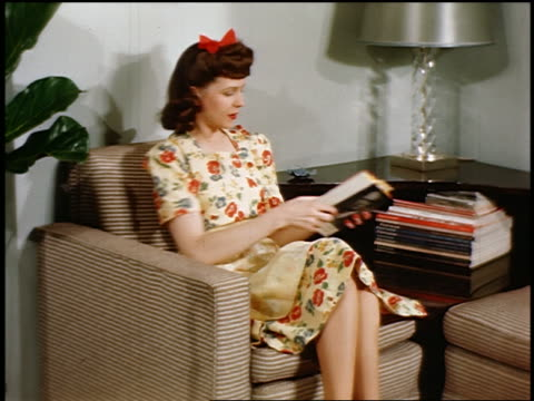 1946 woman sitting in armchair reading stack of books / industrial - stereotypical housewife stock videos and b-roll footage
