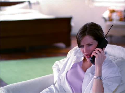 woman sitting in armchair + talking on cordless telephone in loft - schnurloses telefon stock-videos und b-roll-filmmaterial
