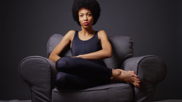 woman sitting in armchair - 座る点の映像素材/bロール