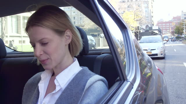 Woman sitting in back seat of car looking out of window, daytime