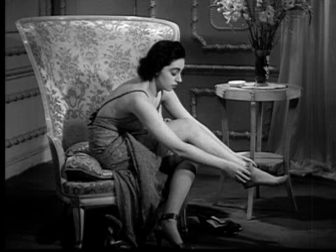 1937 B/W MONTAGE WS Woman (Elaine Barrie) sitting in chair in nightgown, taking off shoes, and rolling off stockings