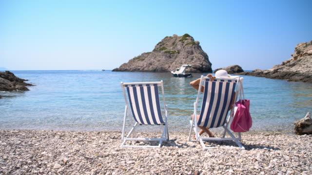 DS Frau sitzend auf Stuhl am idyllischen Strand
